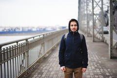 Un hombre joven que se coloca en el puente en la primavera Fotos de archivo libres de regalías