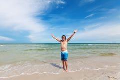 Un hombre joven que se coloca en una playa arenosa. Fotos de archivo libres de regalías