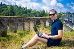 Un hombre joven que se sienta con el puente ferroviario de piedra viejo cercano al aire libre del ordenador portátil Fotos de archivo libres de regalías