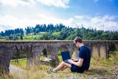 Un hombre joven que se sienta con el puente ferroviario de piedra viejo cercano al aire libre del ordenador portátil Imágenes de archivo libres de regalías