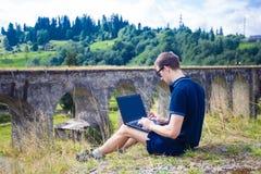 Un hombre joven que se sienta con el puente ferroviario de piedra viejo cercano al aire libre del ordenador portátil Fotografía de archivo