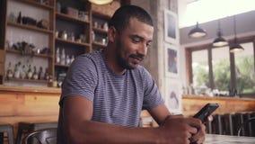 Un hombre joven que se sienta en envío de mensajes de texto del café en el teléfono móvil almacen de video