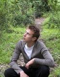 Un hombre joven que se sienta en un bosque del resorte fotos de archivo libres de regalías