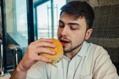 Un hombre joven que se sienta en un restaurante y va a comer la hamburguesa sabrosa Fotografía de archivo