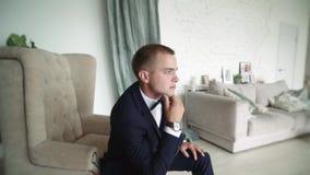 Un hombre joven que se sienta en una silla mira cuidadosamente hacia fuera la ventana Un hombre de negocios en un traje de negoci almacen de video
