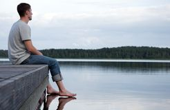 Un hombre joven que se sienta solamente por el agua Fotos de archivo libres de regalías