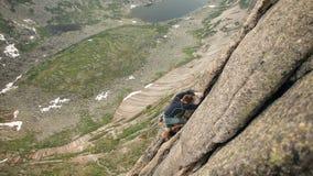 Un hombre joven que sube valeroso una montaña sin una cuerda almacen de metraje de vídeo