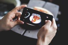 Un hombre joven que toma la foto de la pizza en smartphone, fotografiando la comida con la cámara móvil Visión superior Foto de archivo libre de regalías