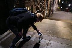 Un hombre joven que toma las fotos en las calles de Edimburgo en la noche Fotos de archivo libres de regalías