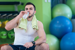 Un hombre joven que toma una rotura en el gimnasio que se sienta en una bola de los pilates con una botella de agua Imagen de archivo libre de regalías