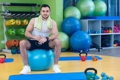Un hombre joven que toma una rotura en el gimnasio que se sienta en una bola de los pilates con una botella de agua Imágenes de archivo libres de regalías