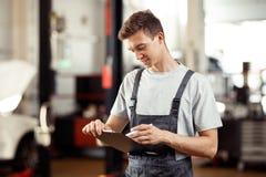 Un hombre joven que trabaja en un servicio de reparación del coche está completando un formulario imagen de archivo