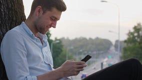 Un hombre joven que usa un móvil al aire libre metrajes