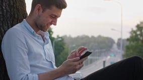 Un hombre joven que usa un móvil al aire libre almacen de metraje de vídeo