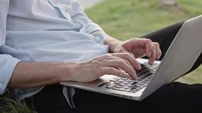 Un hombre joven que usa un ordenador portátil al aire libre almacen de metraje de vídeo