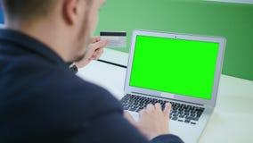 Un hombre joven que usa un ordenador portátil con una pantalla verde almacen de video