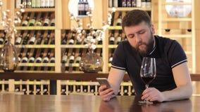 Un hombre joven que usa un smartphone mientras que bebe un vino rojo, hombre solo con un vidrio de vino rojo, hombre joven en a almacen de video