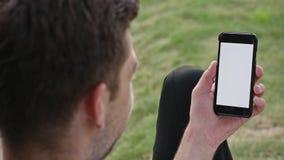 Un hombre joven que usa un teléfono al aire libre almacen de video