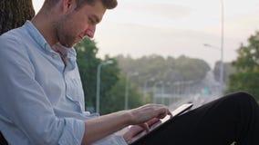 Un hombre joven que usa una tableta al aire libre metrajes