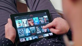 Un hombre joven que usa una tableta dentro imagen de archivo libre de regalías