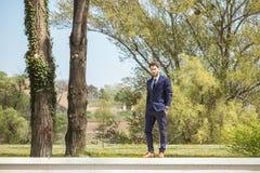 Un hombre joven, ropa formal se adapta a los zapatos, colocándose en la pared, natu Fotografía de archivo