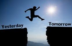 Un hombre joven salta en medio ayer y mañana sobre el sol y a través en el hueco de la silueta de la colina que iguala el cielo c Foto de archivo libre de regalías