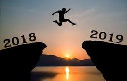 Un hombre joven salta entre 2018 y 2019 años sobre el sol y a través en el hueco de la silueta de la colina Imagen de archivo libre de regalías