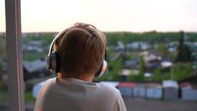 Un hombre joven se coloca cerca de la ventana y pone los auriculares para escuchar la música Fondo borroso con la puesta del sol, metrajes