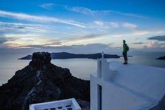 Un hombre joven se coloca en el tejado blanco de una iglesia en la isla romántica famosa de Santorini fotos de archivo