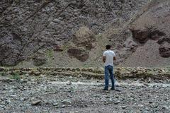 Un hombre joven se coloca en la montaña fotografía de archivo