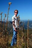 Un hombre joven se está colocando en un campo de flores seco imágenes de archivo libres de regalías