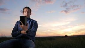 Un hombre joven se está sentando en la puesta del sol y está hablando en una llamada video en una tableta Cielo hermoso detrás metrajes