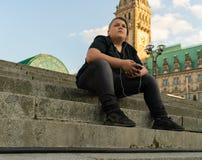 Un hombre joven se está sentando en los pasos y está mirando delantero pensativo Fotos de archivo