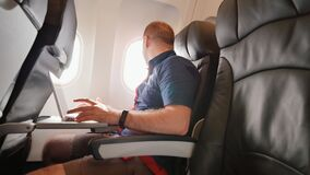 Un hombre joven se sentaba en el avión y trabajaba en su ordenador portátil antes de salida metrajes