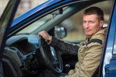Un hombre joven se sienta detrás de la rueda de un coche trabajo Imagen de archivo