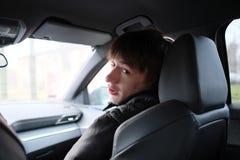Un hombre joven se sienta en un coche Fotografía de archivo