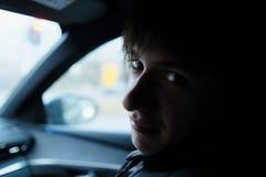 Un hombre joven se sienta en un coche Foto de archivo libre de regalías