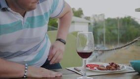 Un hombre joven se sienta en una tabla en un restaurante de la terraza almacen de video