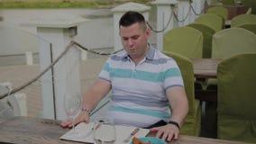 Un hombre joven se sienta en una tabla en un restaurante de la terraza metrajes