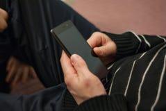 Un hombre joven, sentándose en el sofá para descansar con un smartphone en la ha Imagenes de archivo