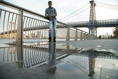 Un hombre joven sienta y admira la vista del ` s Williamsburg Brid de NYC Imagen de archivo