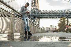 Un hombre joven sienta y admira la vista del ` s Williamsburg Brid de NYC Imagen de archivo libre de regalías
