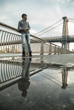 Un hombre joven sienta y admira la vista del ` s Williamsburg Brid de NYC Imagenes de archivo
