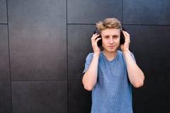 Un hombre joven sonriente con el suyo observa escuchar cerrado la música en sus auriculares en el fondo de una pared gris Imagen de archivo libre de regalías