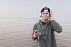 Un hombre joven sonriente escucha la música en los auriculares y sostiene un smartphone en el fondo ligero Fotografía de archivo libre de regalías
