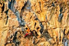 Un hombre joven sube en una pared rocosa en la puesta del sol foto de archivo