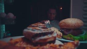 Un hombre joven toma la comida del refrigerador en la noche metrajes