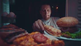 Un hombre joven toma la comida del refrigerador en la noche almacen de metraje de vídeo