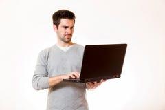 Un hombre joven trabaja en un ordenador portátil mientras que se coloca Imagen de archivo libre de regalías