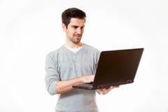 Un hombre joven trabaja en un ordenador portátil mientras que se coloca Fotografía de archivo